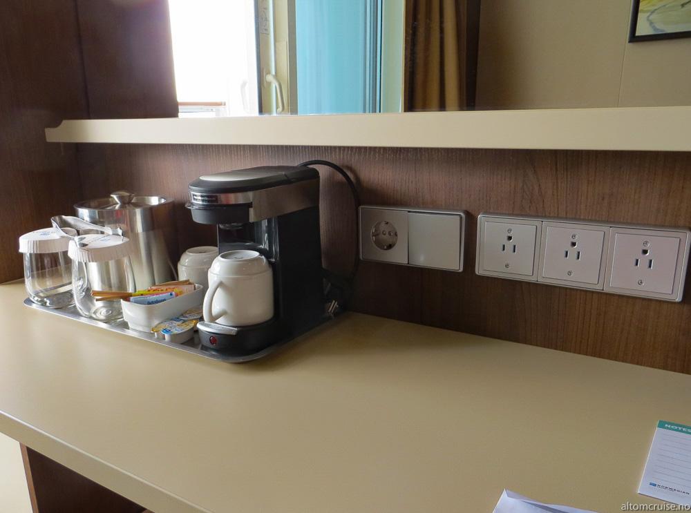 Kaffemaskin og strømuttak på pulten. Legg merke til at det bare er et europeisk og 3 amerikanske